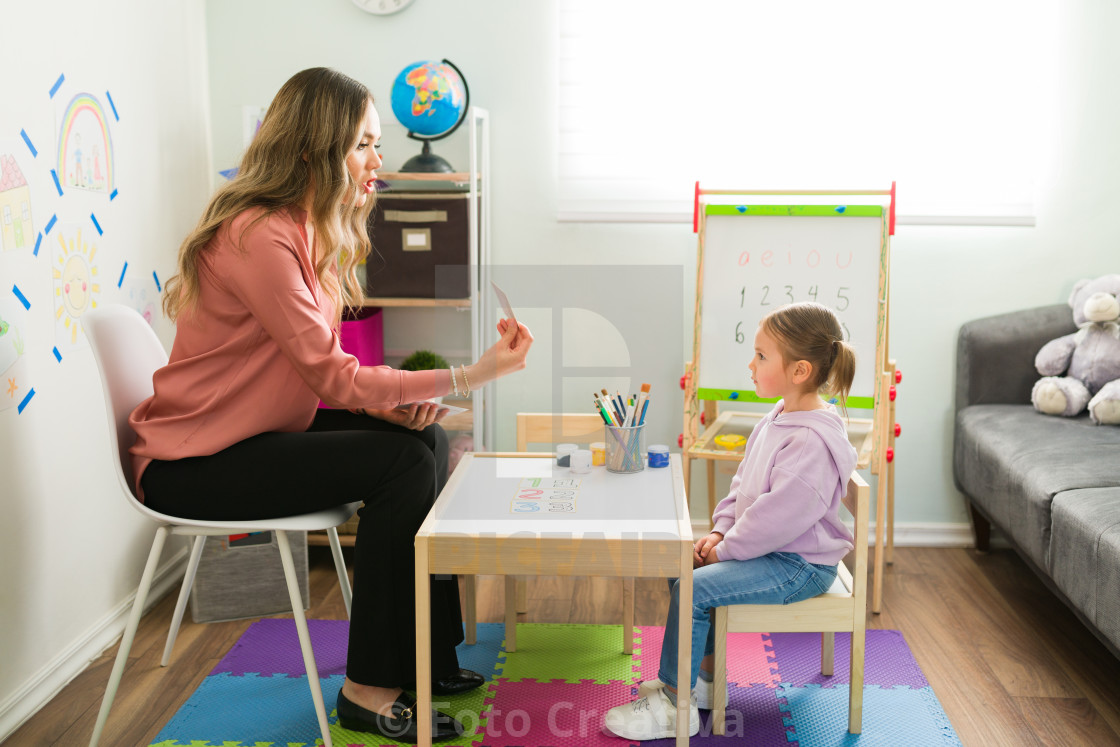 """Preschool girl learning how to read with a female tutor at home"" stock image"
