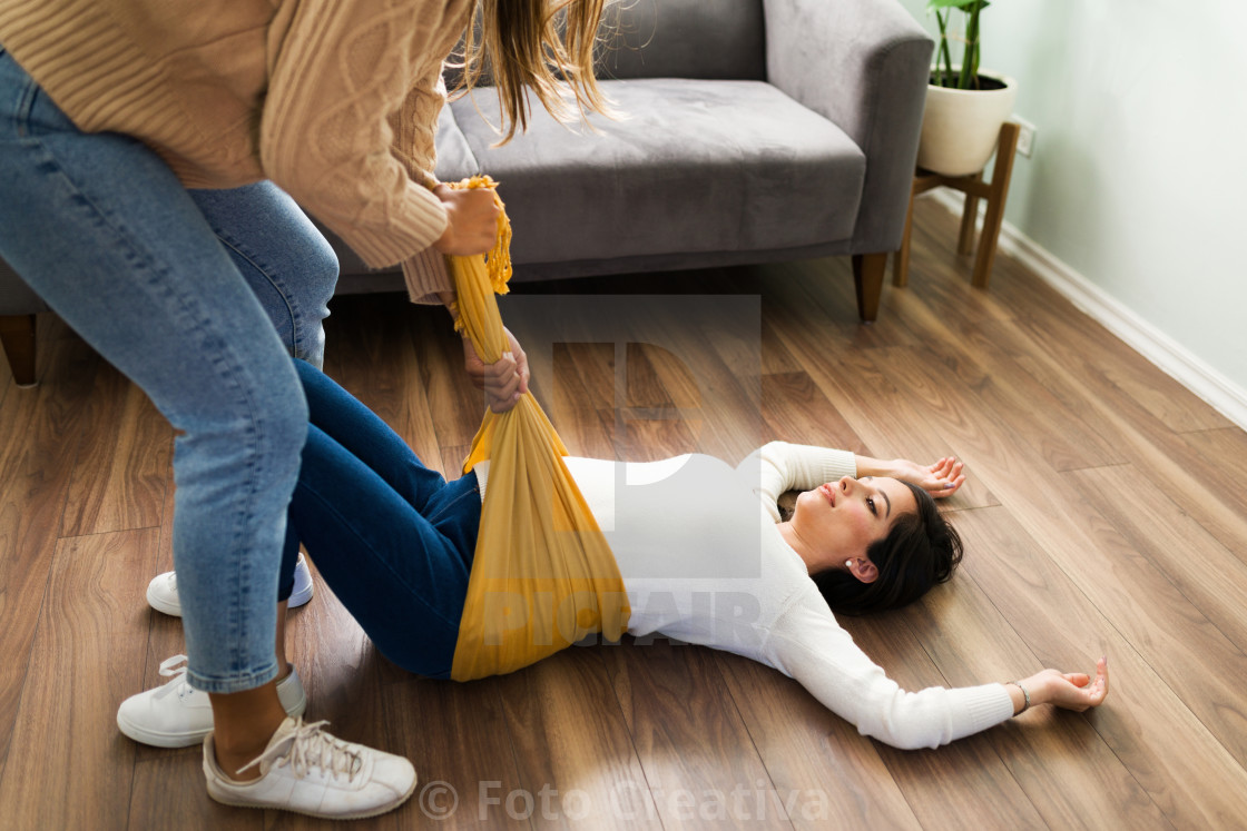 """Latin doula trying to relieve the back pain of an expectant mother"" stock image"