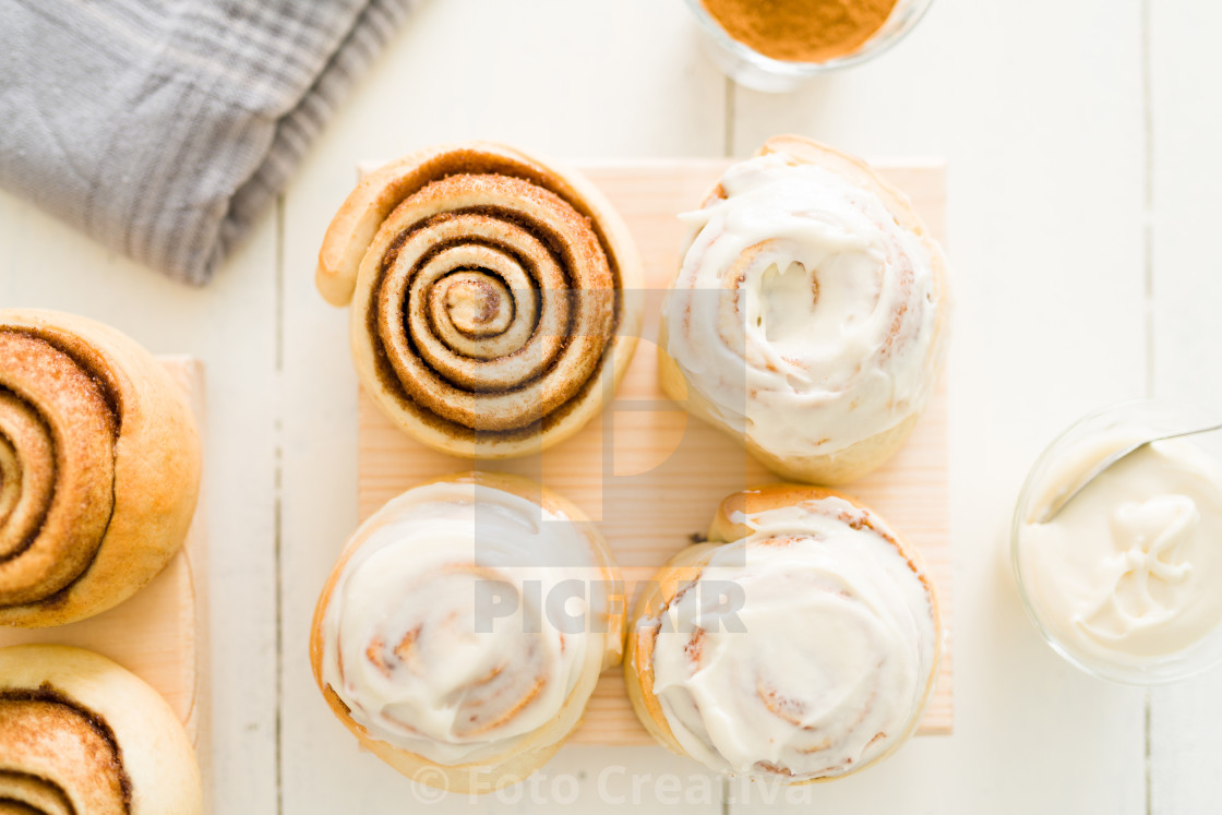 """Flat lay of baked sweet rolls decorated with white icing"" stock image"