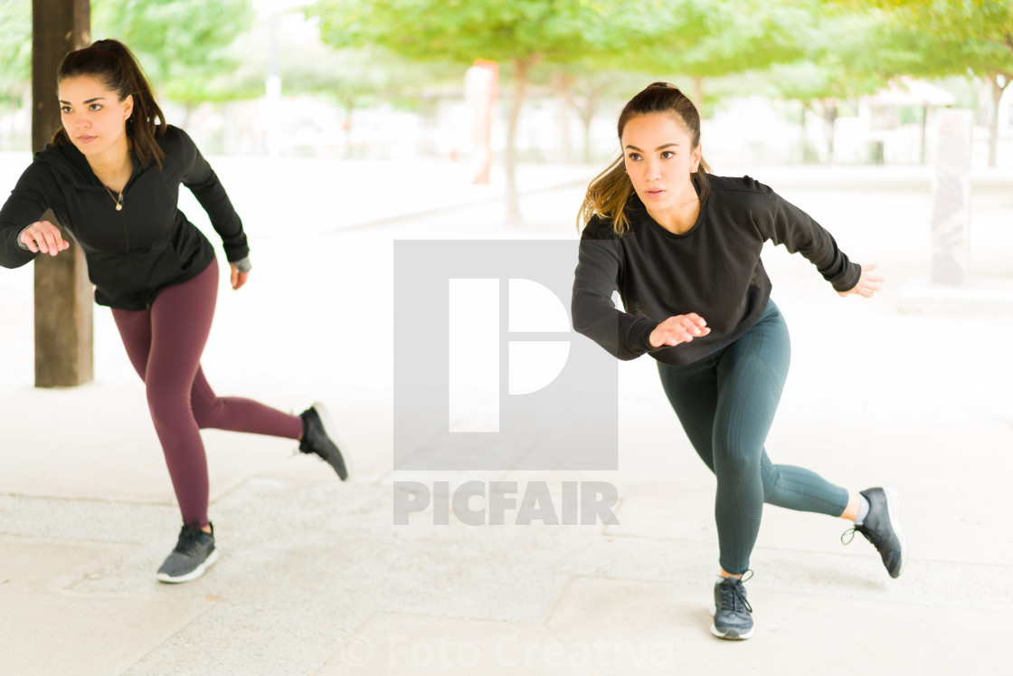 """Attractive workout partners working out at the park"" stock image"