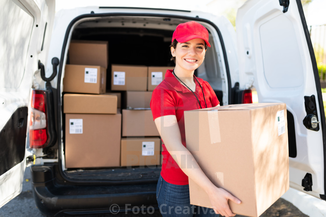 """Female courier and driver carrying a bunch of packages"" stock image"