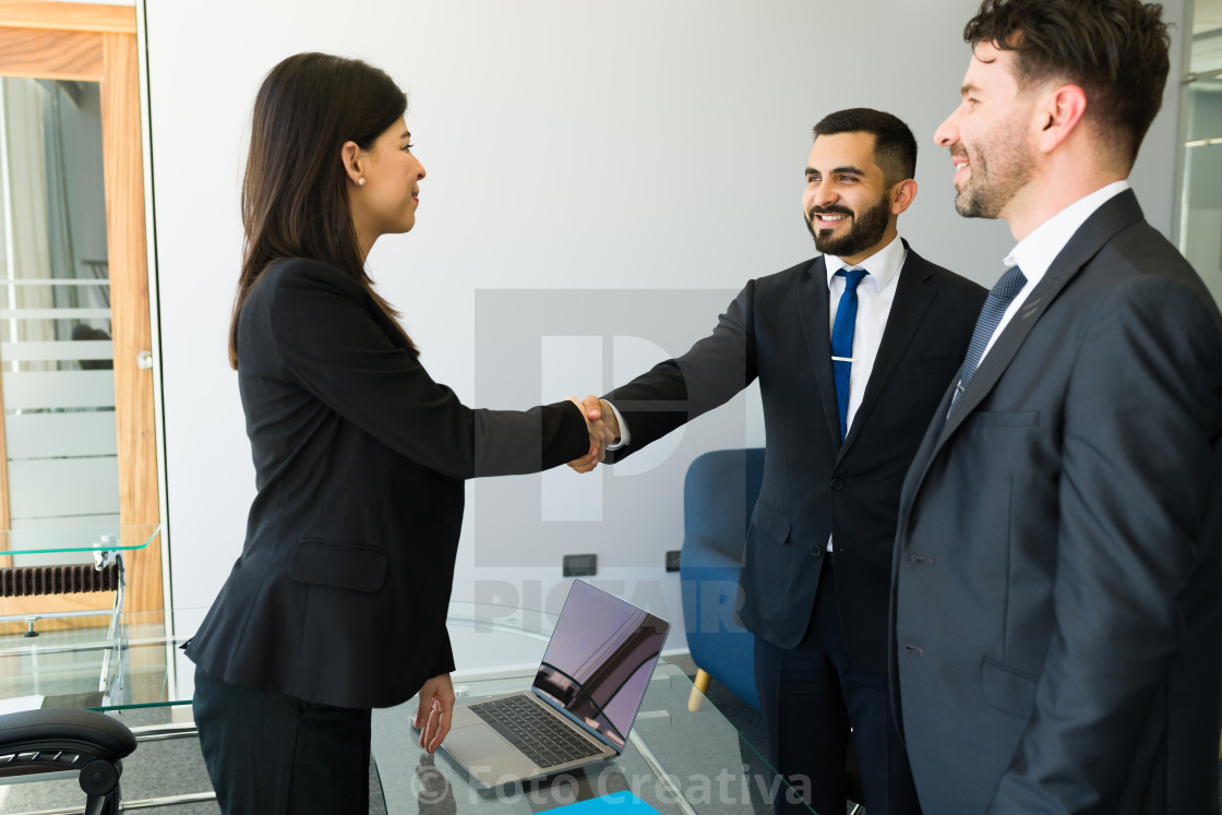 """Business executives shaking hands at the office"" stock image"