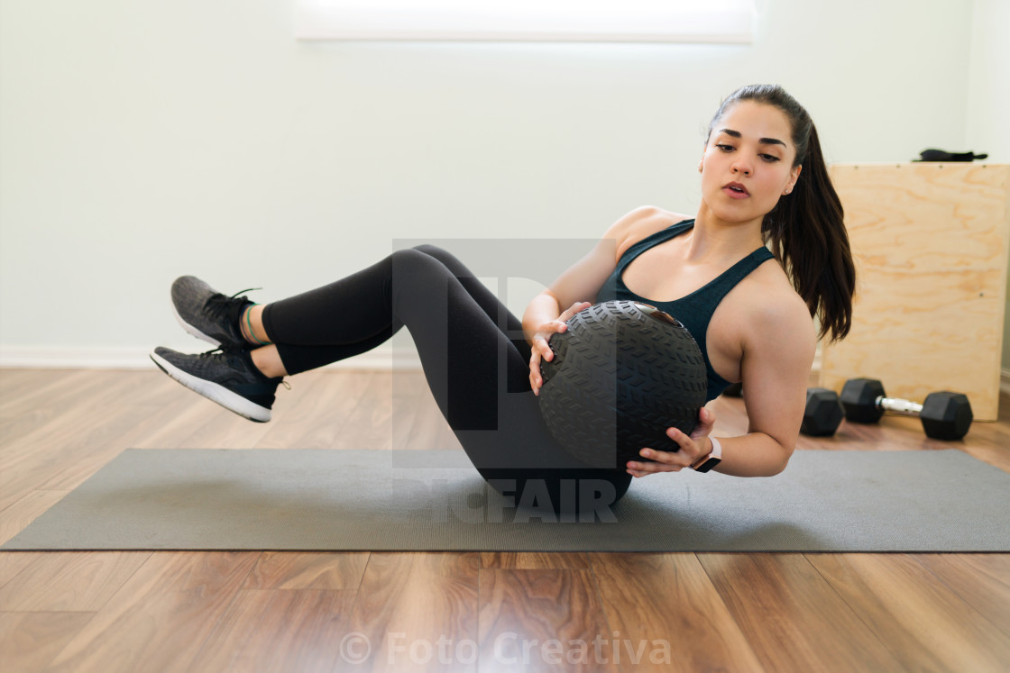 """""""Athletic young woman practicing side sit-ups"""" stock image"""
