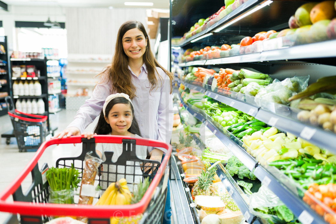 """""""Mom and daughter pushing a shopping cart"""" stock image"""