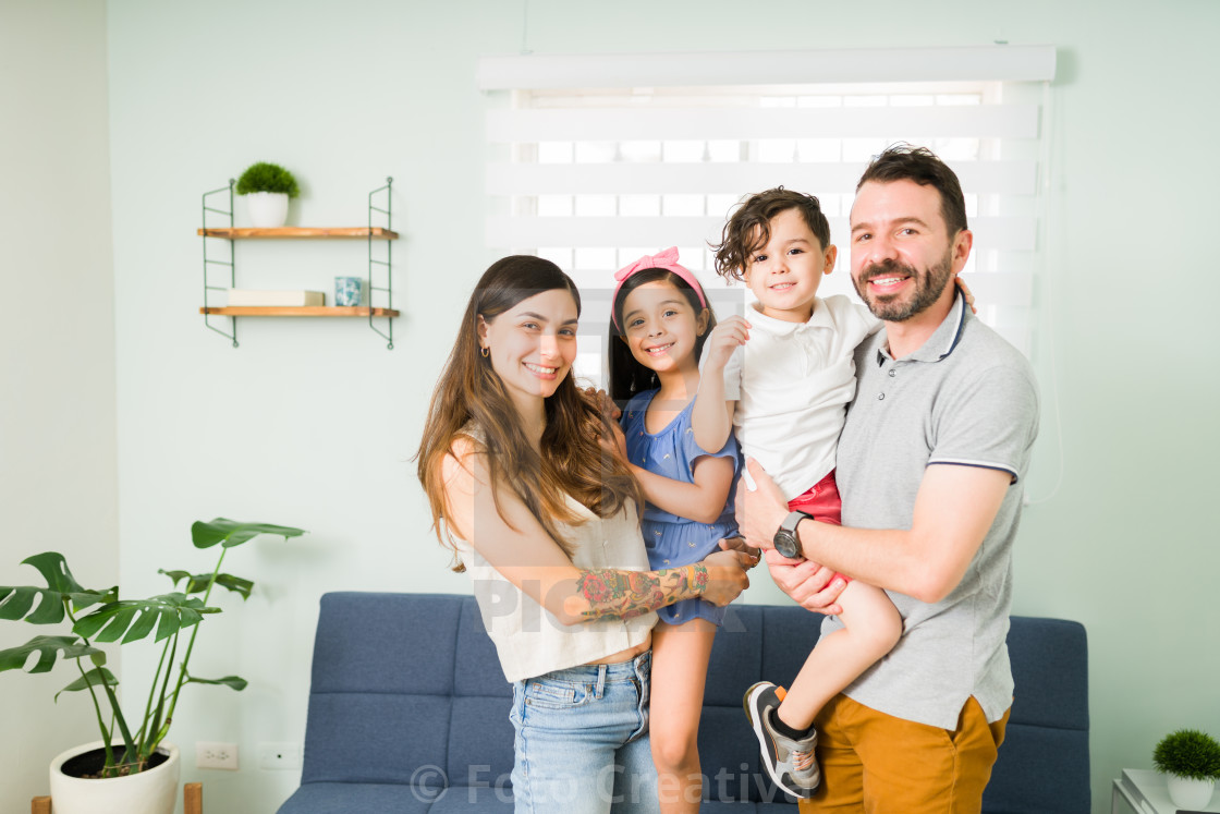 """""""Young mom, dad and kids posing for a photo"""" stock image"""
