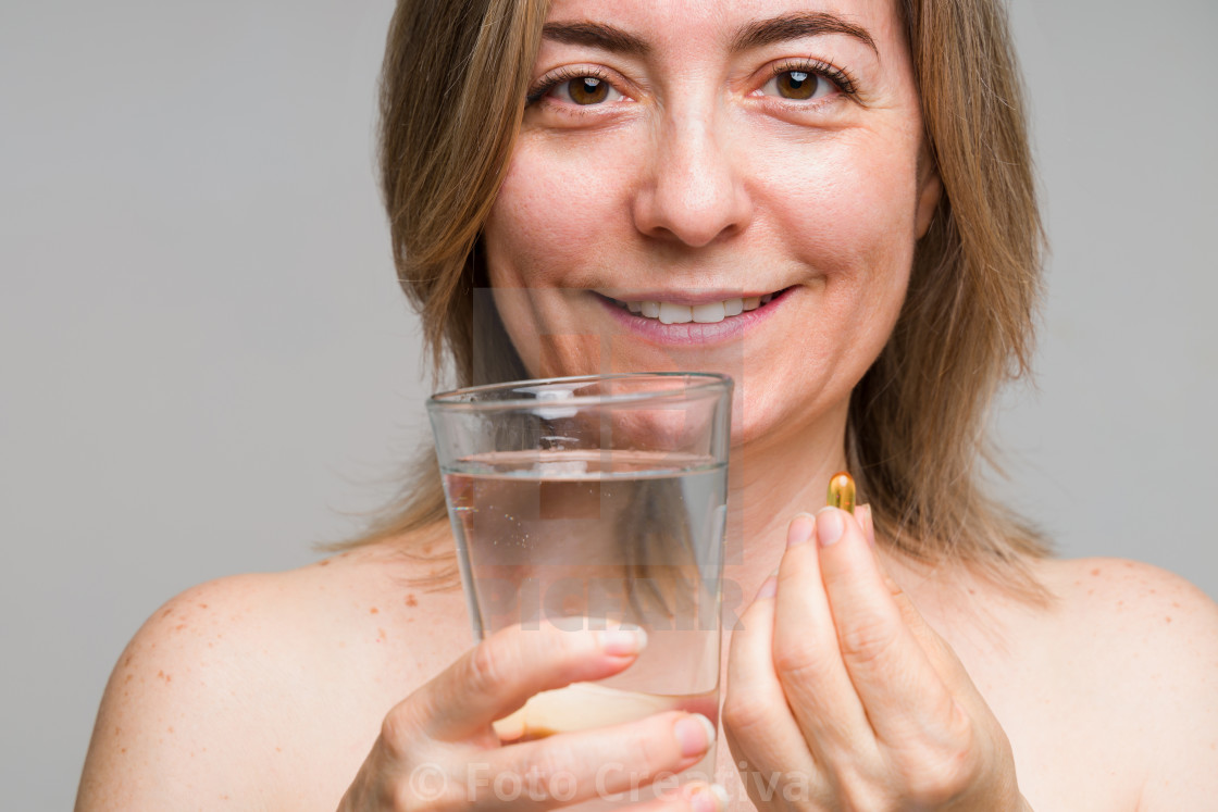 """""""Portrait of a woman in her 50s taking vitamins"""" stock image"""