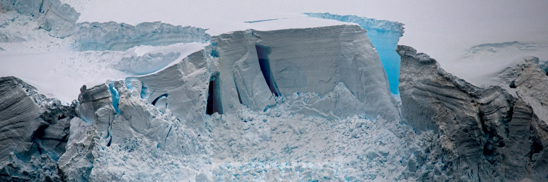 """Blue crack in the ice cliff"" stock image"