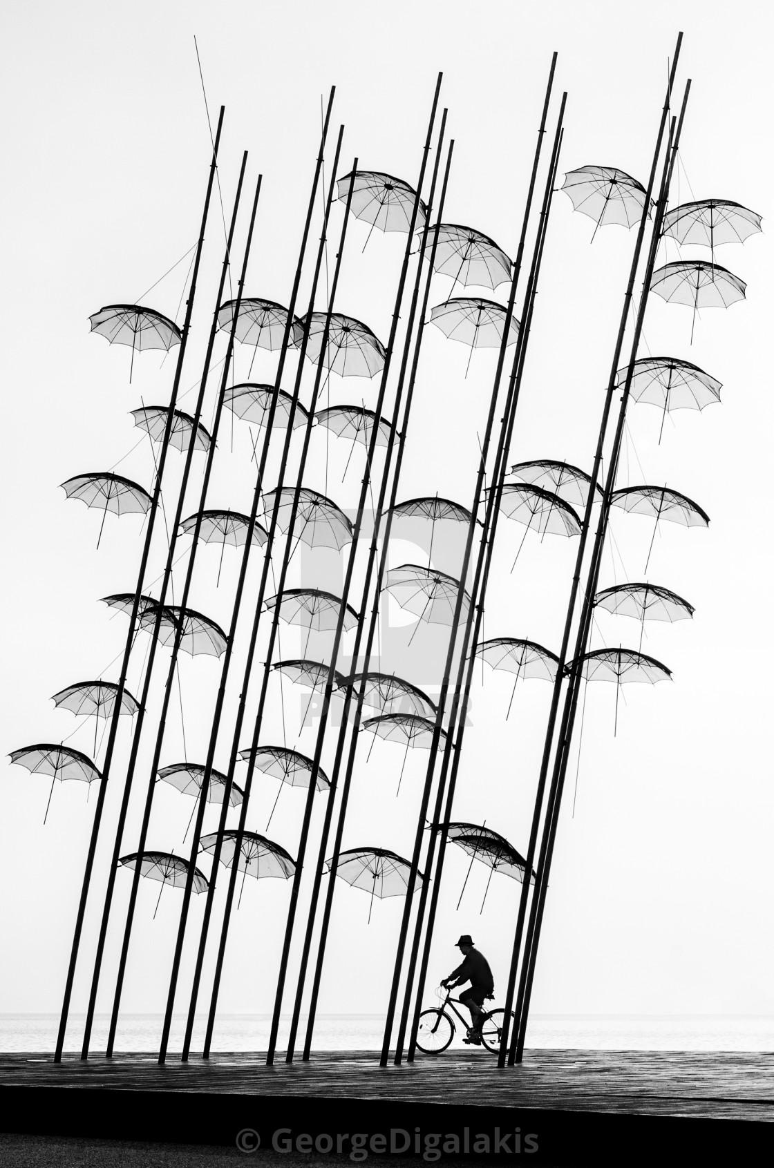 """Bicyclist under the umbrellas"" stock image"