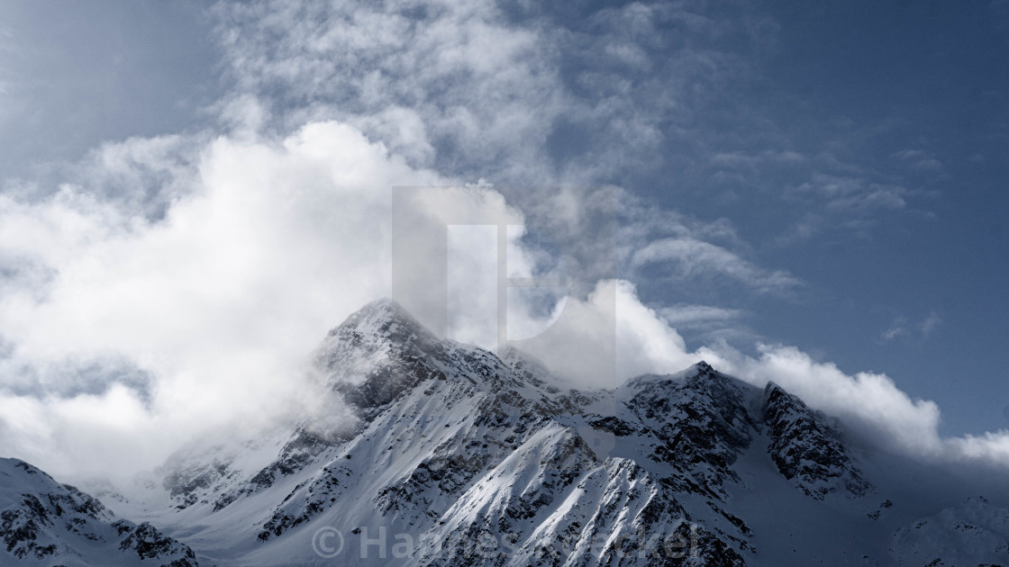 """""""Snowy mountains and cloudy sky"""" stock image"""
