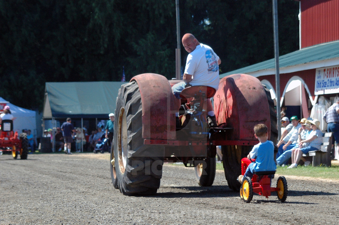 """Gotta start'em early! Boy following dad's tractor."" stock image"