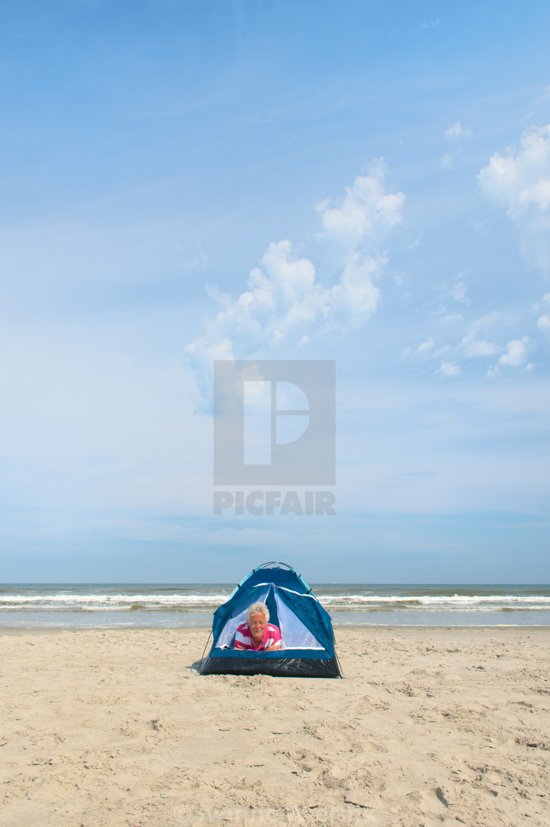 """Man camping in shelter at the beach"" stock image"