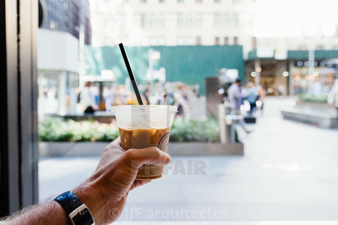 """""""Man hand holding a plastic cup of iced coffee on urban background"""" stock image"""