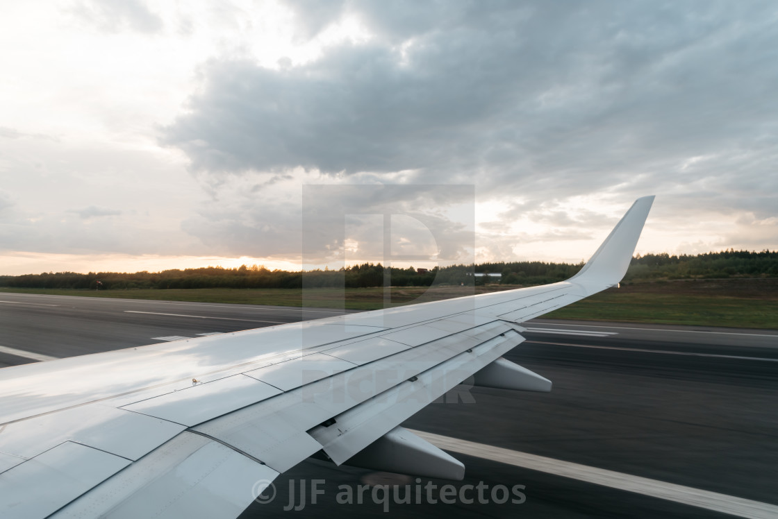 """""""Wing of a flying airplane landing on runway"""" stock image"""