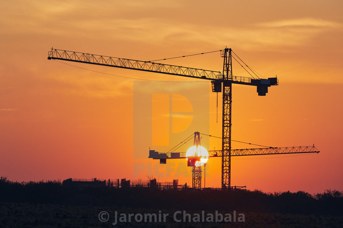 """Building activity on contruction site at sunrise"" stock image"