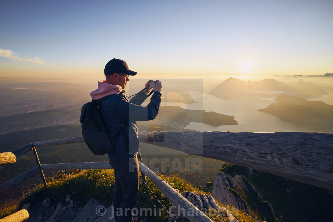 """Man photographing landscape at beautiful sunrise"" stock image"