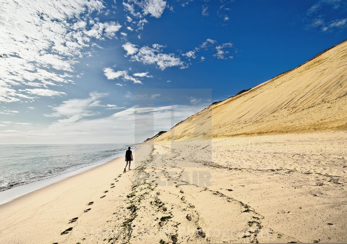 """Woman walking on beach along huge sand dune cliffs at Long Nook Beach, Cape Cod National Seashore, Truro, Cape Cod, Massachusetts, USA."" stock image"