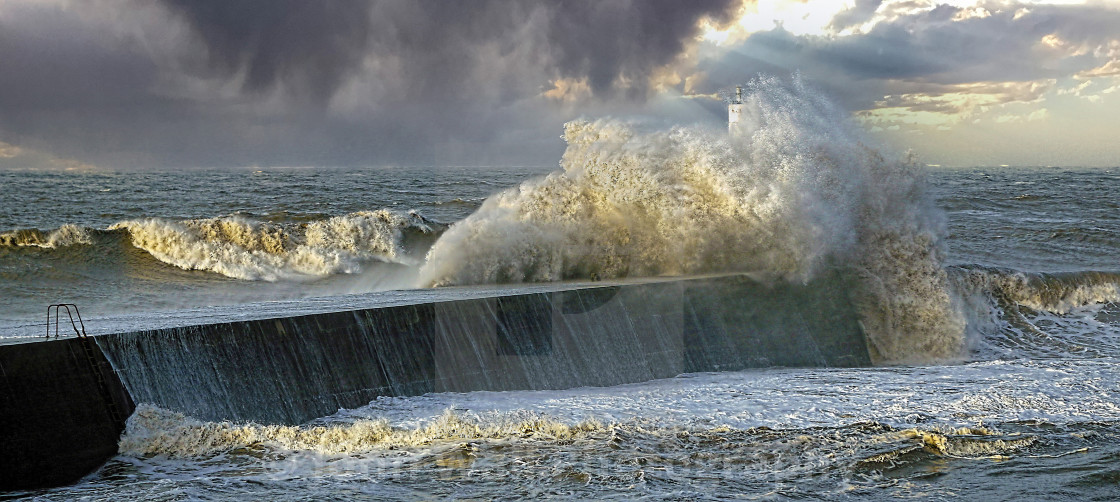 """Water breaking over the harbour wall"" stock image"