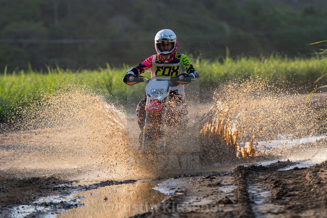 Motorcycle riding through mud puddle