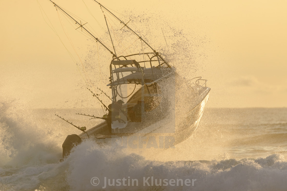 """Fishing ski boat punching through a wave"" stock image"