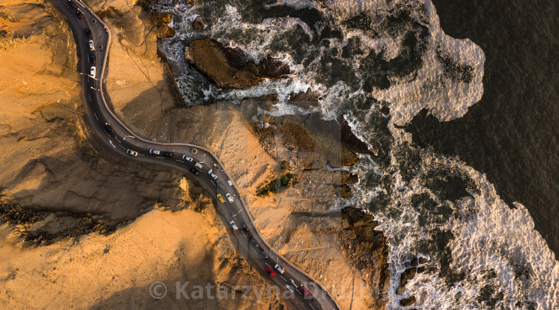 """Aerial top-down view on the road at the cliffs next to the rocky coast with traffic during the sunset"" stock image"