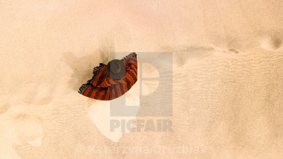 """""""Aerial top-down view on a solo traveler standing on sand dune wearing an Andean styled poncho and a brown hat."""" stock image"""