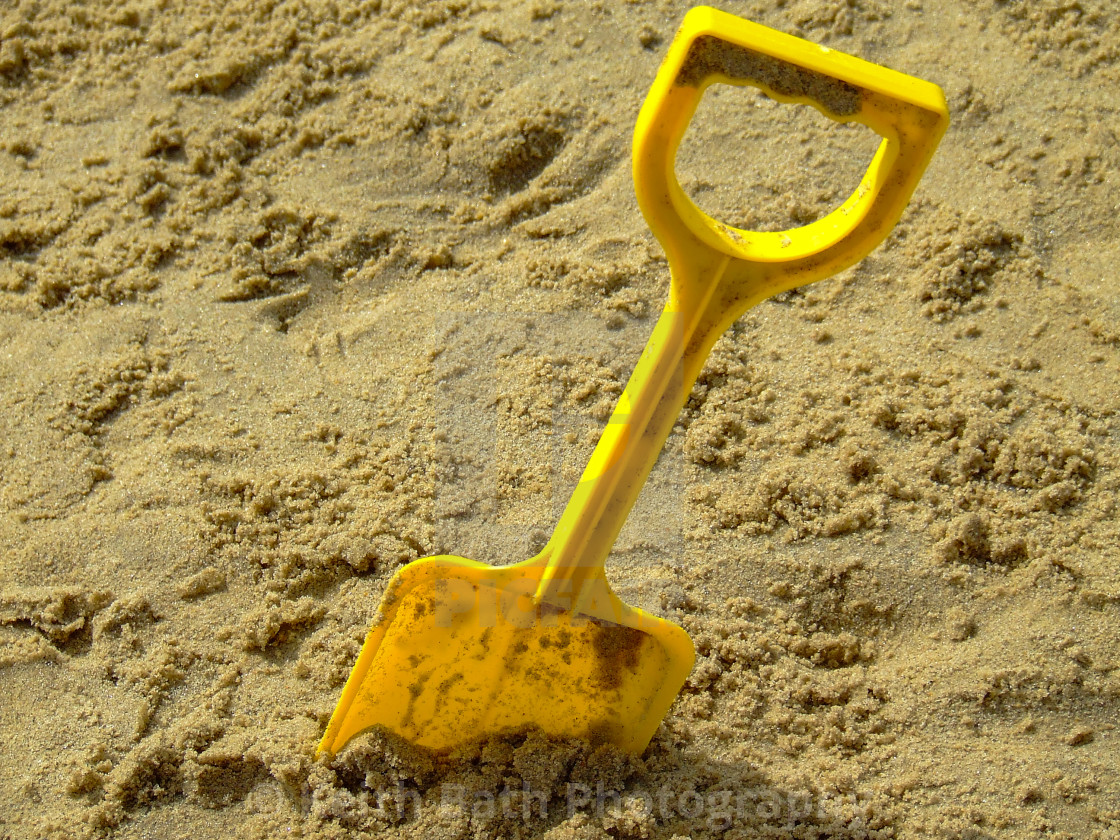 """An abandoned yellow spade in the sand on the beach"" stock image"