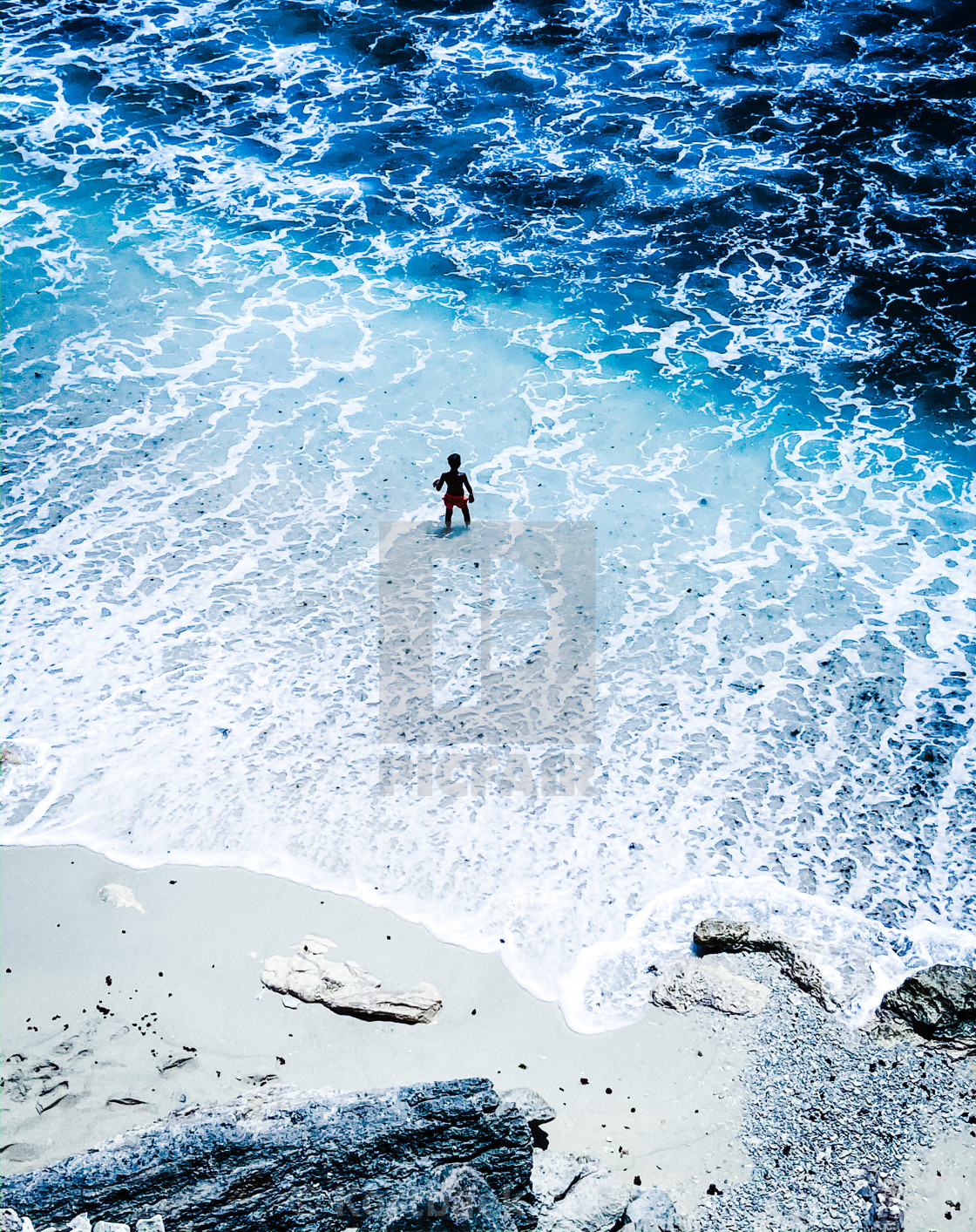 """""""A child plays by the waves on Dream Beach, on the island of Nusa Lembongan, Indonesia"""" stock image"""