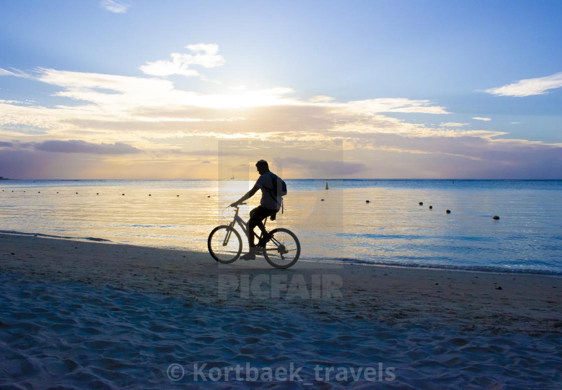 """Boy riding a bike on Troux aux Biches Beach, Mauritius"" stock image"