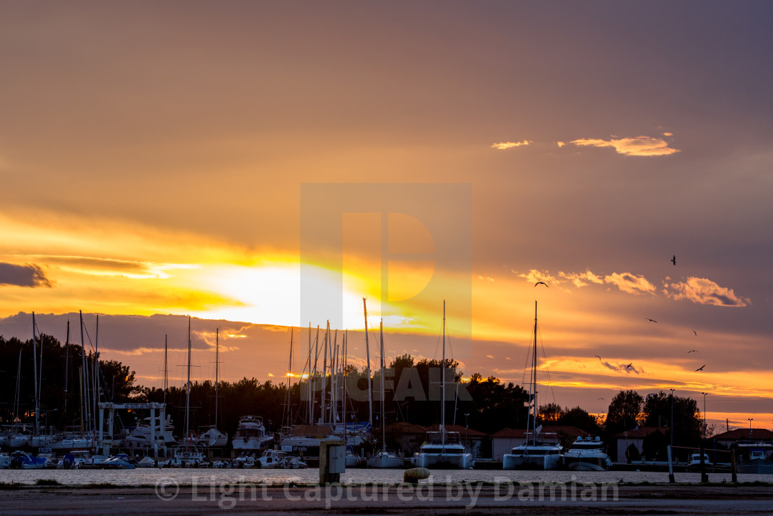 """Orange golden sunset over port of Porto Lagos"" stock image"
