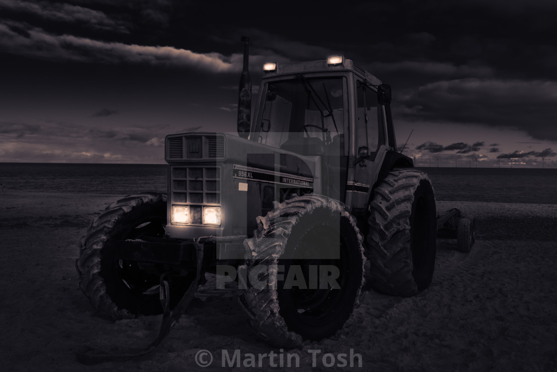 """""""Moody mono of old tractor on beach."""" stock image"""