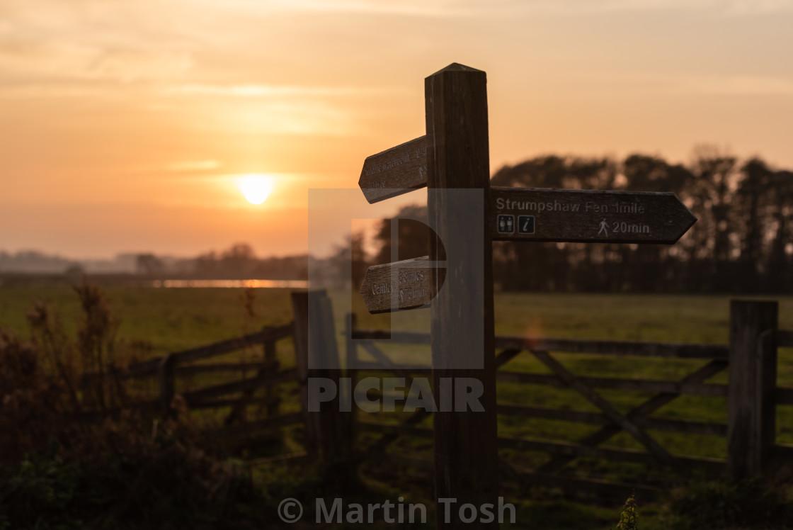 """Fingerpost footpath sign at sunset, Buckenham Marshes."" stock image"