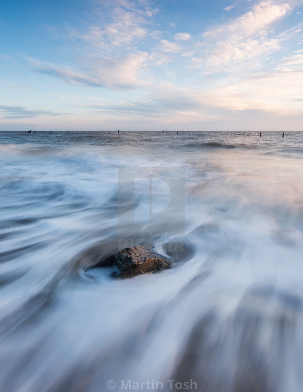 """soft wave motion around Happisburgh beach rock"" stock image"