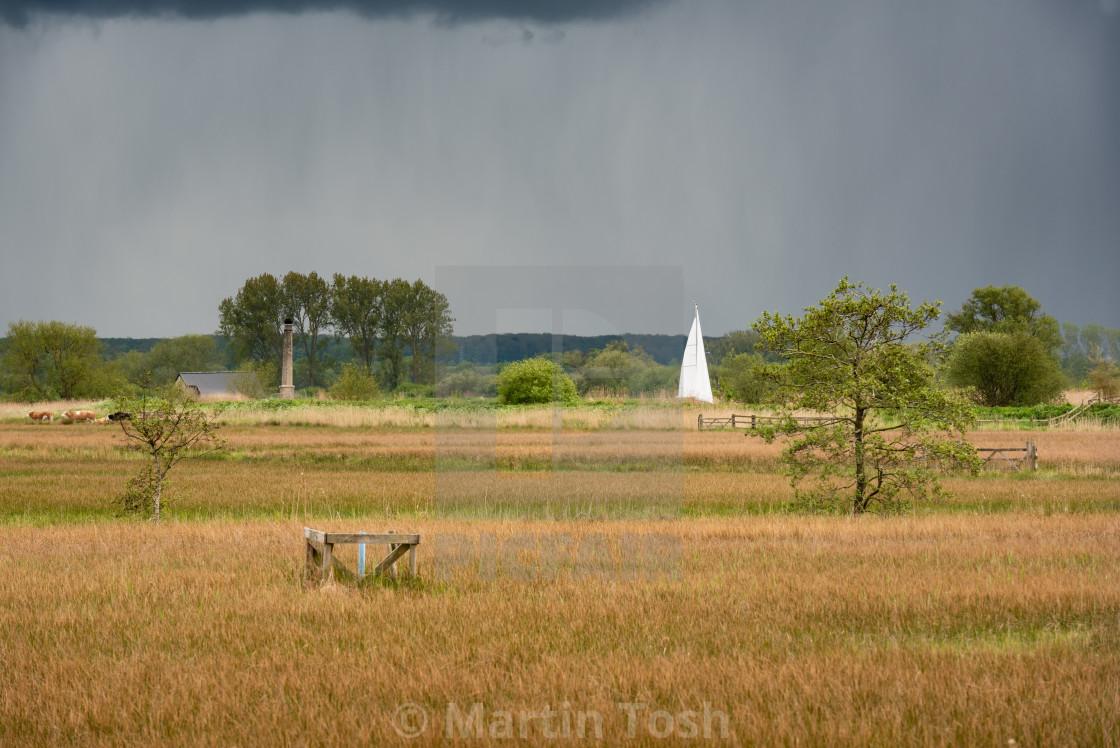 """Sailboat in Norfolk Broads marshland, rainy skies"" stock image"