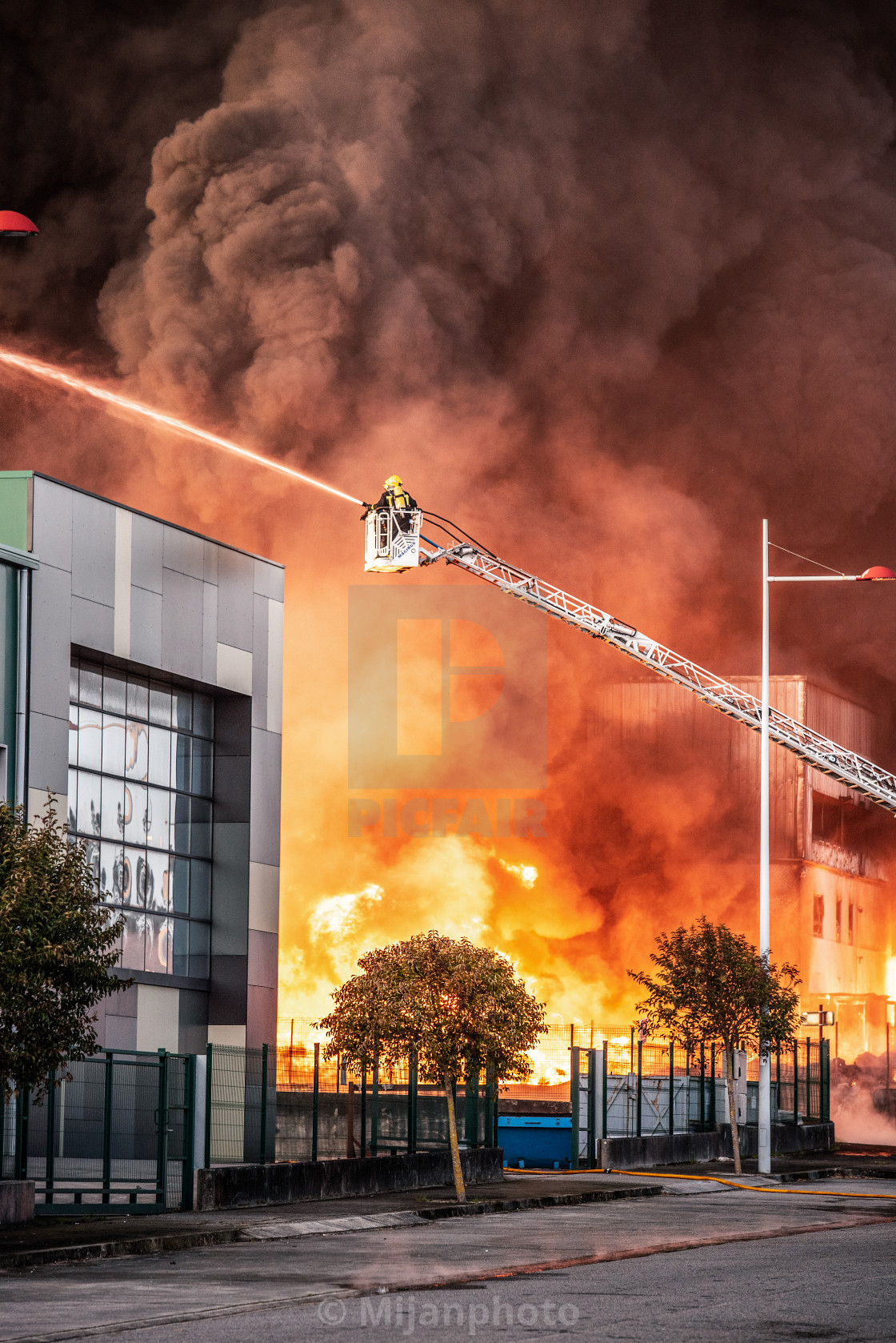 """""""firefighters against a fire in an industrial unit facility"""" stock image"""