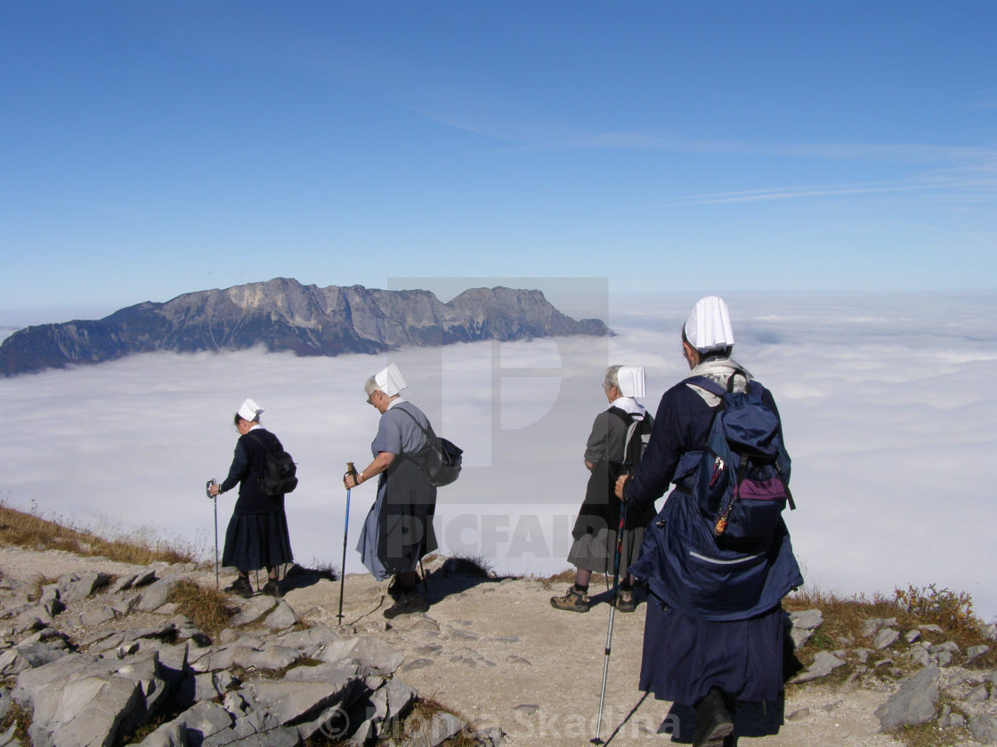 """""""Nuns hike in the mountains above the clouds"""" stock image"""