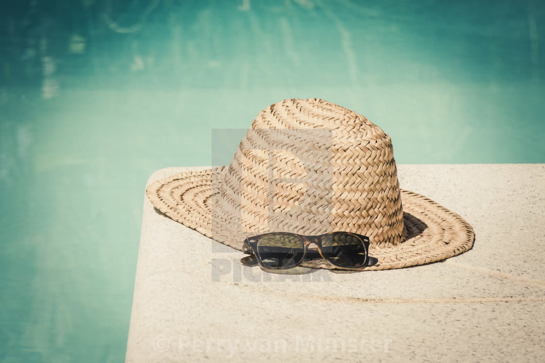 """Vintage straw hat with sun glasses at the border of a swimming pool in summer."" stock image"