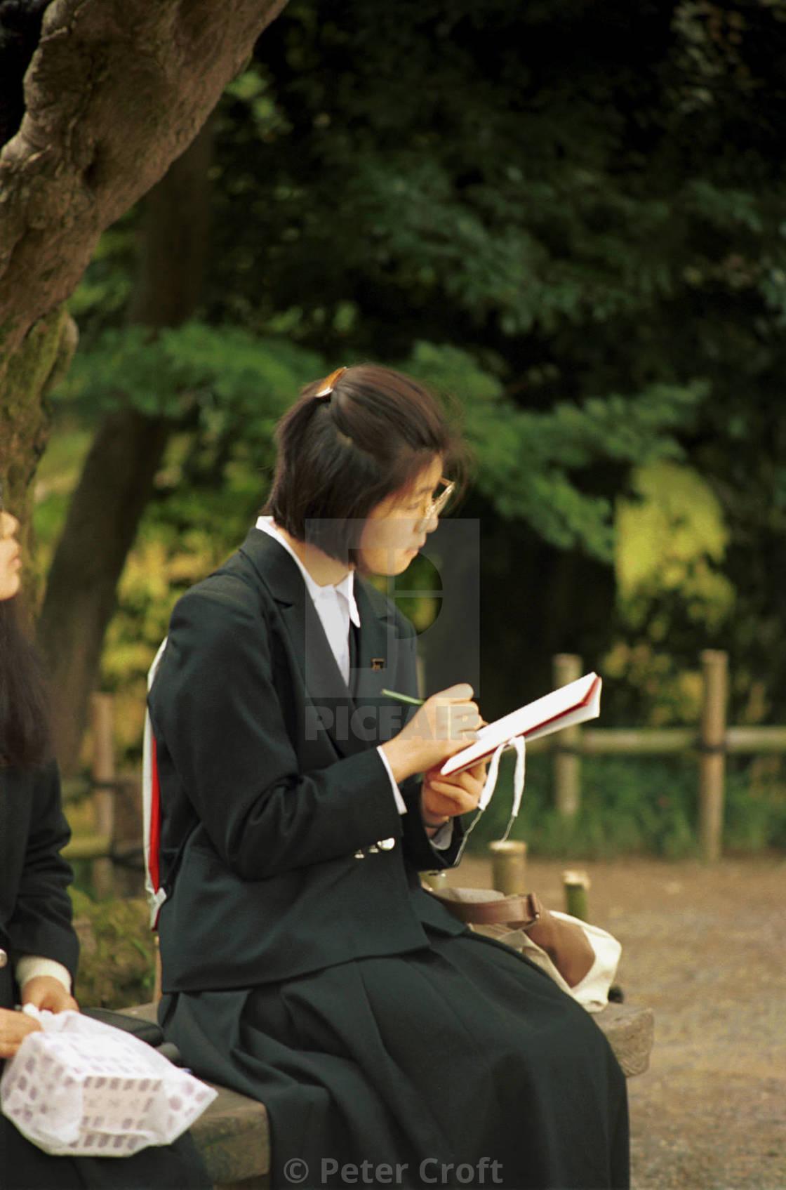 """A schoolgirl studies in a park, Kanazawa, Japan."" stock image"