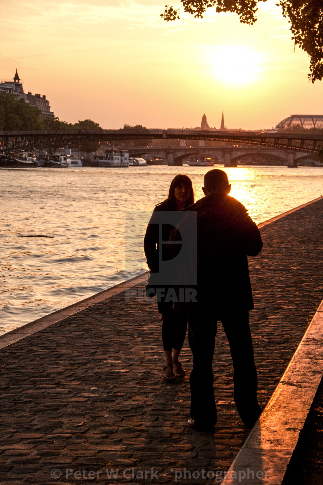 """""""Couple Walking by the River Seine, Paris at Sunset."""" stock image"""