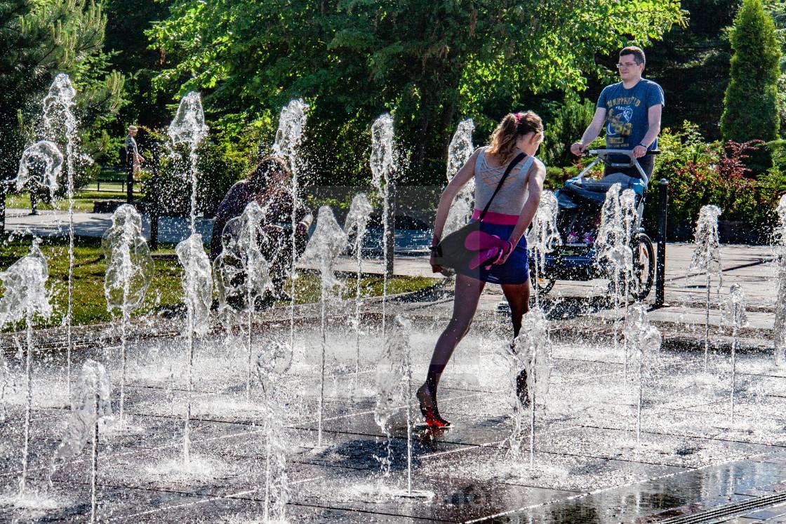 """Girl running through The Fountain on The Promenade, Swinoujscie, Poland."" stock image"