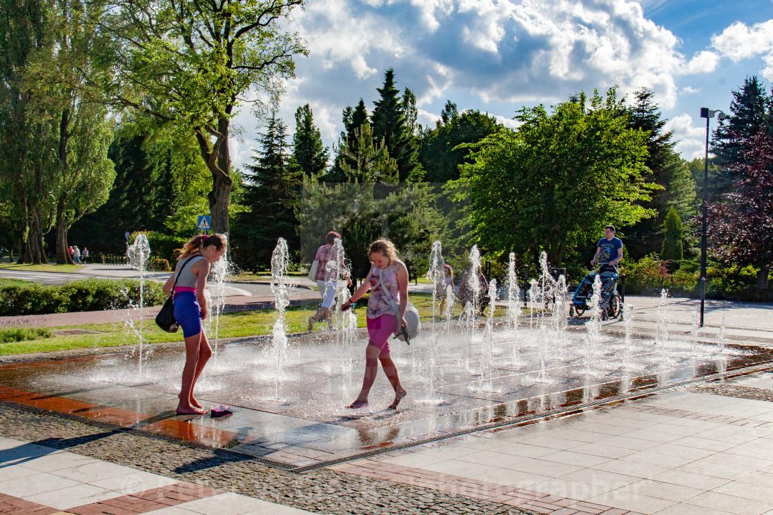 """Girls running through The Fountain on The Promenade, Swinoujscie, Poland."" stock image"