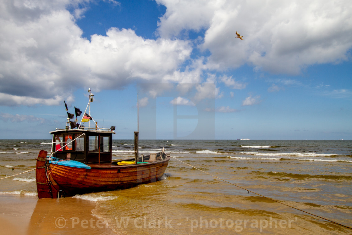"""Photographs of Ahlbeck a Seaside Resort on the Baltic Sea Coast, Germany. Small fishing boat with Flags anchored on the beach."" stock image"