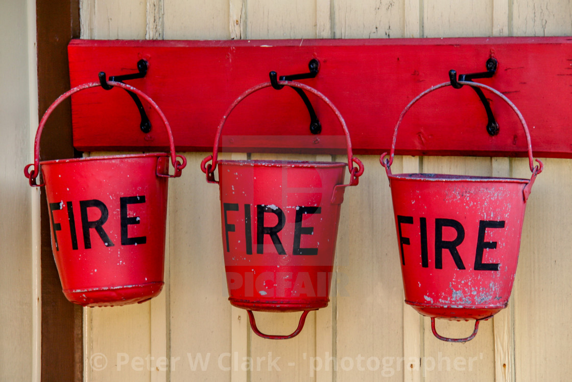 """Embsay and Bolton Abbey Steam Railway. Three Hanging Red Fire Buckets."" stock image"