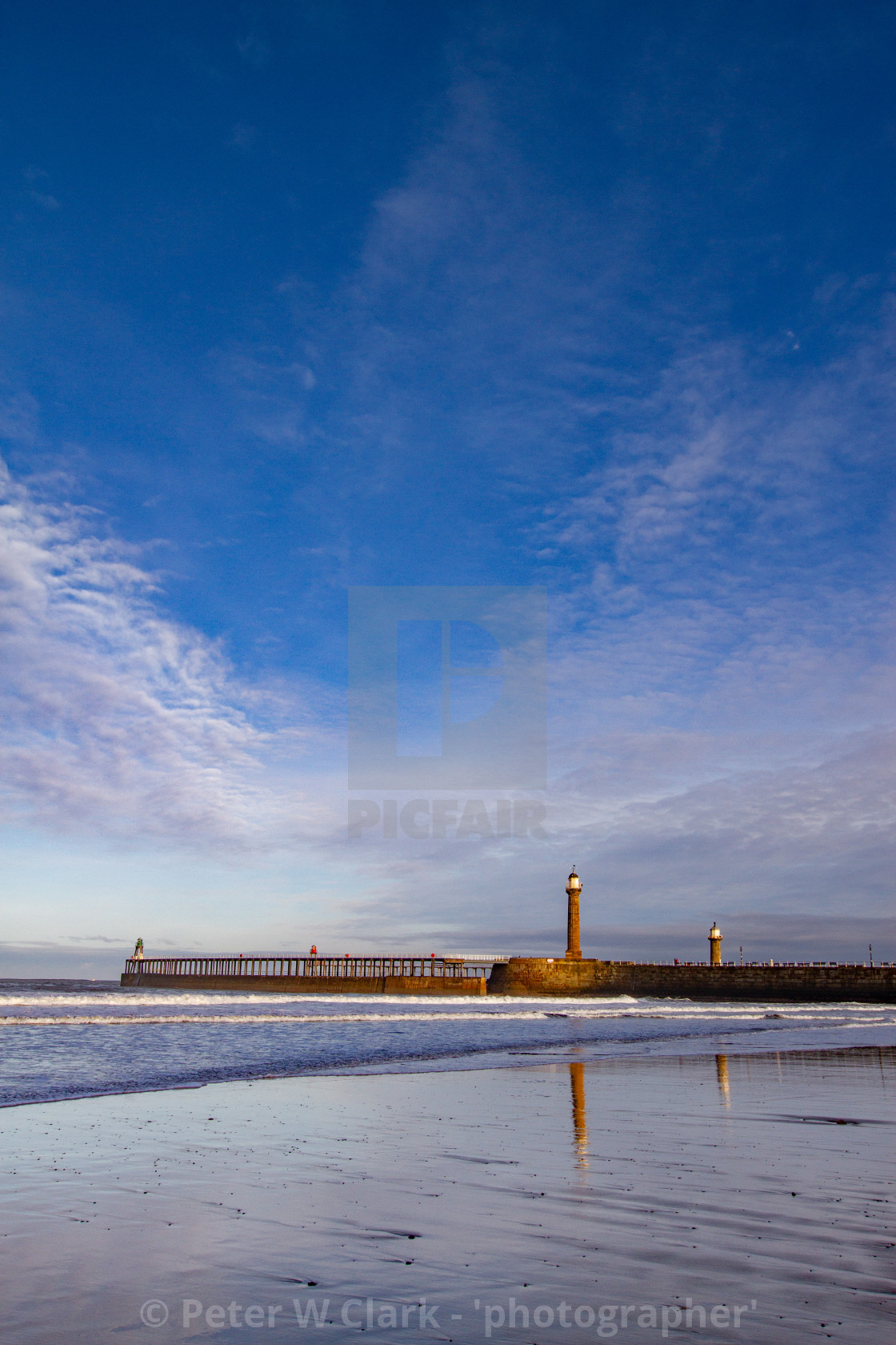 """Whitby, UK, Beach, Pier,lighthouse and Reflection. Blue Sky and Copy Space."" stock image"