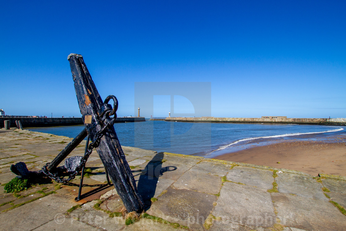 """Whitby,UK,Yorkshire,East coast, Old Anchor on Tate Hill Pier. Collier Hope Beach in the Background."" stock image"