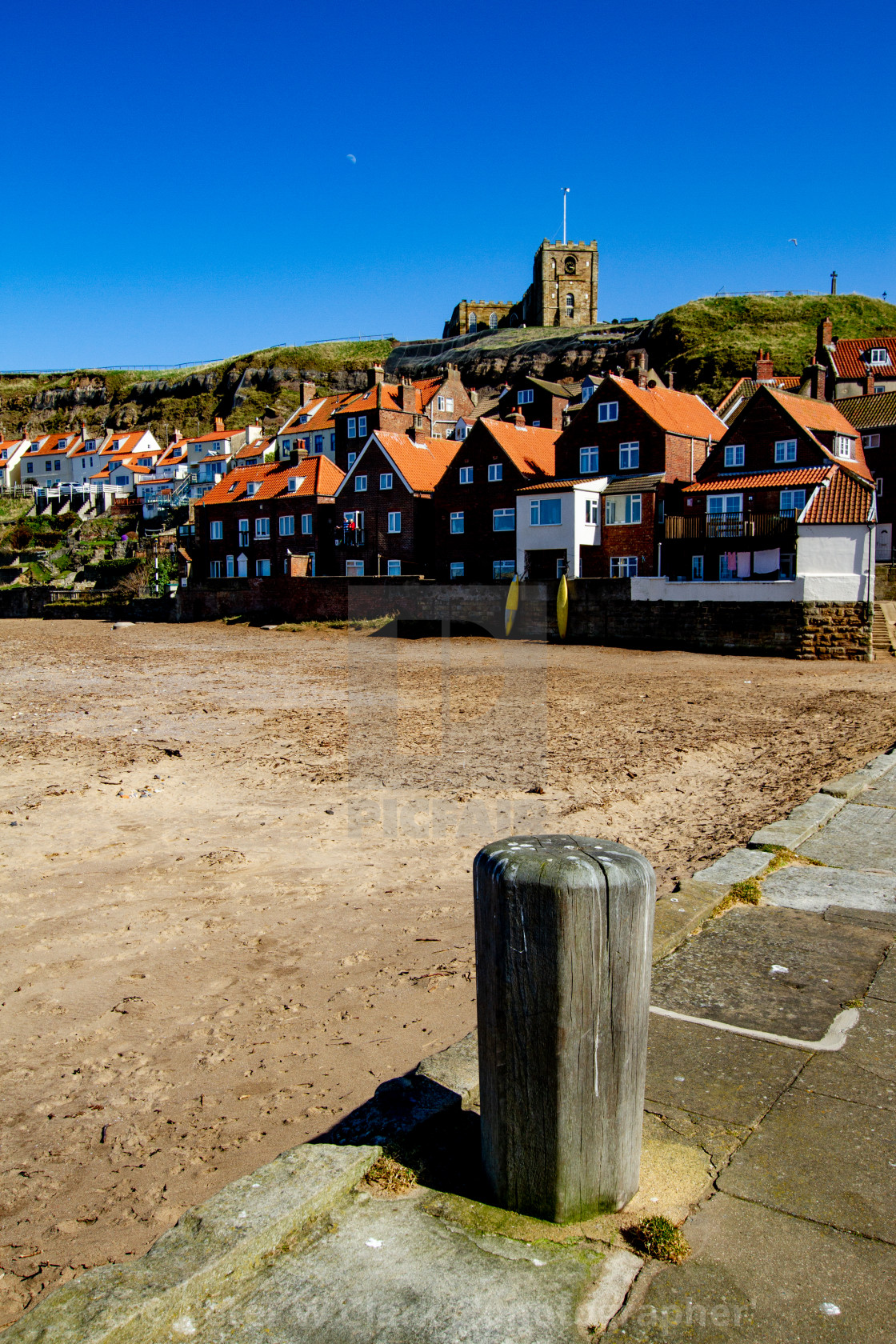 """Whitby,UK,Yorkshire,East coast, Mooring Post on Tate Hill Pier. Collier Hope Beach and St Mary's Church in the Background. Photographed April 2013."" stock image"