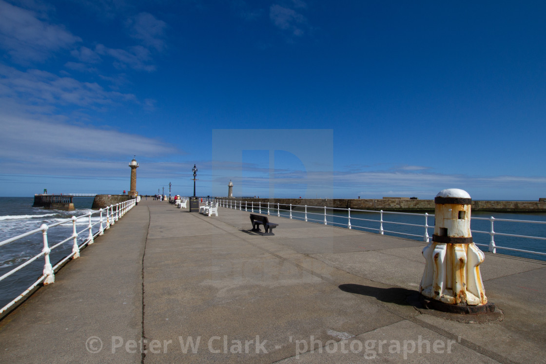 """Whitby,UK,Yorkshire,East coast, White Capstan on the Harbour Wall, Lighthouse in the Background."" stock image"