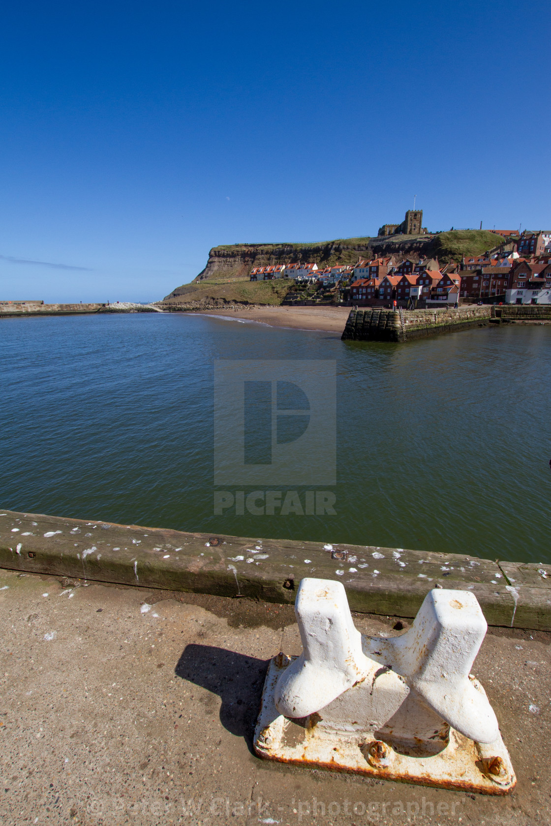 """Whitby,UK,Yorkshire,East coast, View across the Lower Harbour towards Tate Hill Pier and Sands. St Mary's Church in the background, ship Mooring Bollard in the Foreground. Photograph taken on a sunny day, April 2013"" stock image"