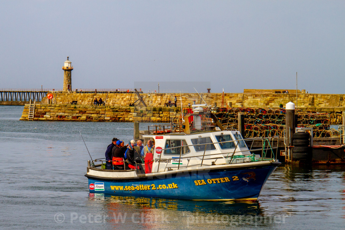 """Sea Otter 2 Returning to Whitby Harbour on Yorkshires East Coast after a Fishing Trip. Pier and Lighthouse in the Background."" stock image"