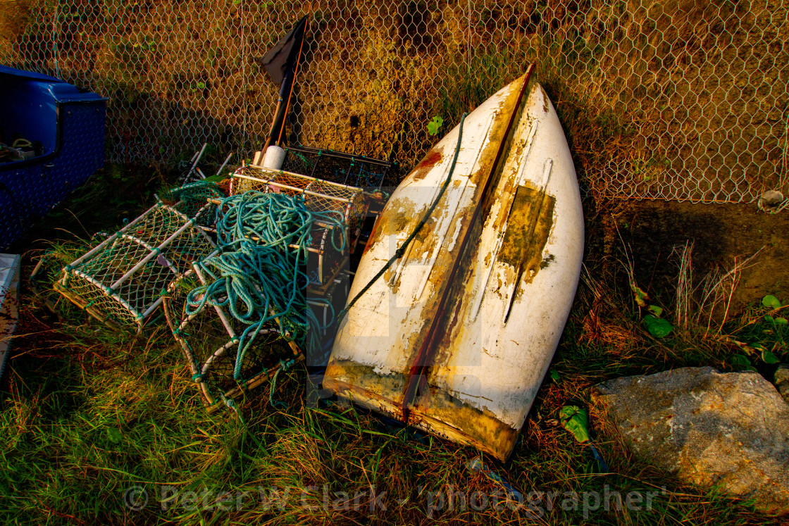 """Overturned dinghy, Rope coil and Lobster pot at Robin Hoods Bay, Yorkshire East Coast, England."" stock image"