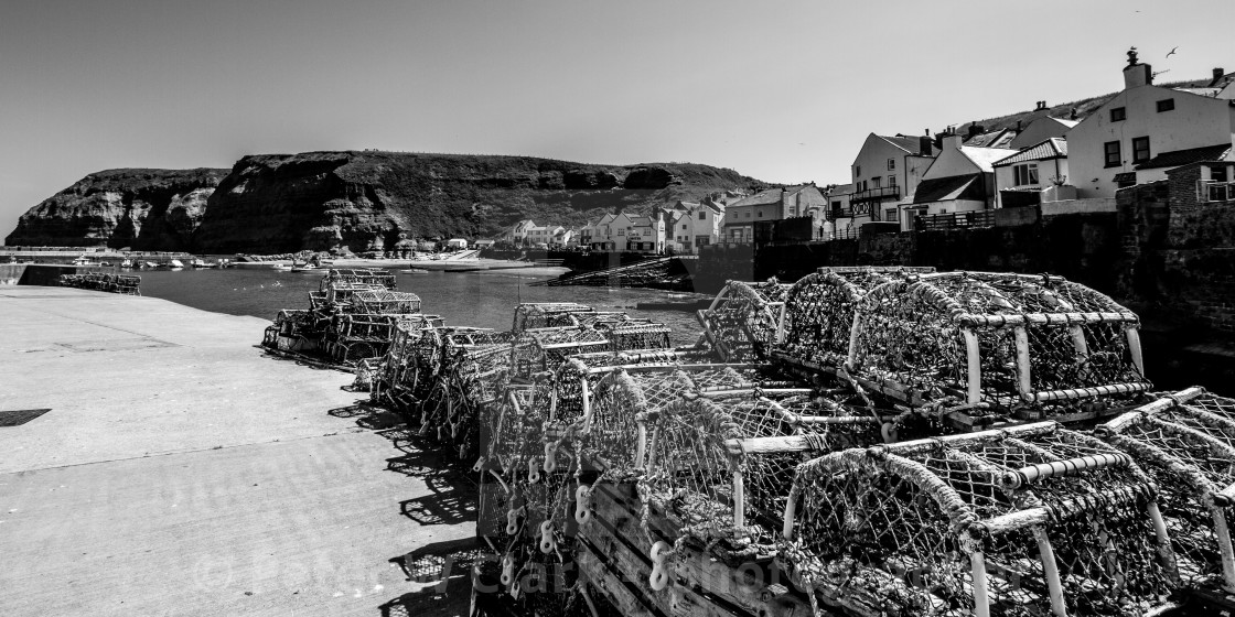 """""""Lobster Pots Stacked on North Side of Staithes Harbour, Yorkshire, England. (monochrome)"""" stock image"""